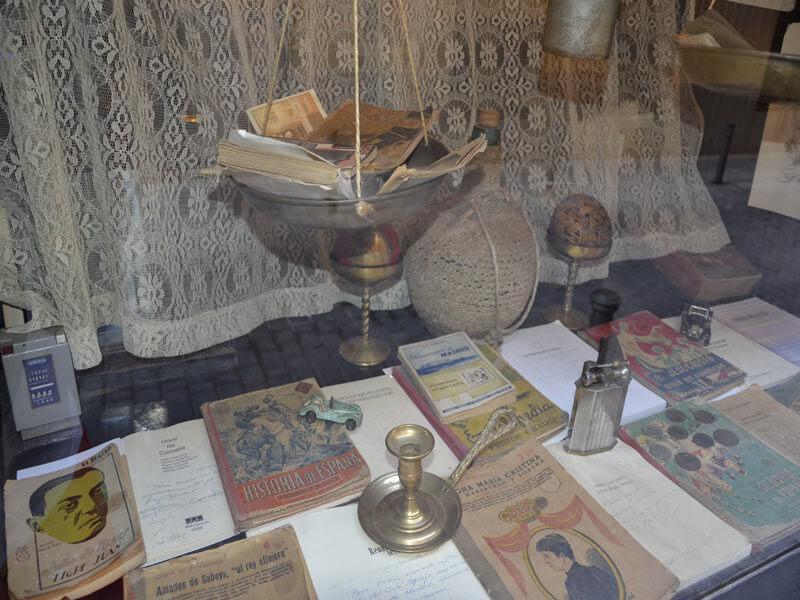 Mostrador de Café Ajenjo con libros y objetos de coleccionista de principios del siglo XX